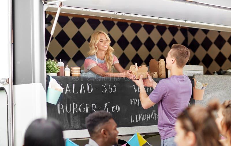 Πωλήτρια στο φορτηγό τροφίμων που εξυπηρετεί τον αρσενικό πελάτη στοκ εικόνες