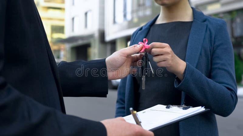 Πωλητής αυτοκινήτων που δίνει τα κλειδιά για το νέο όχημα στην ευτυχή κυρία, αυτοκινητική αγορά στοκ εικόνες