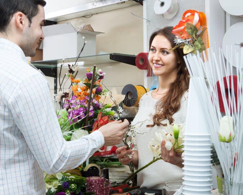 Πωλητής γυναικών που προσφέρει τον άνδρα λουλουδιών στοκ φωτογραφία με δικαίωμα ελεύθερης χρήσης
