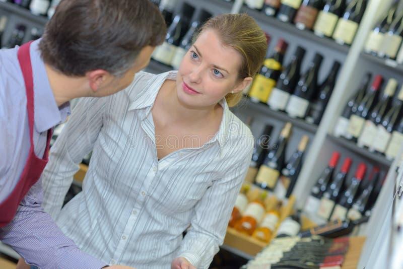 Πωλητής νεαρών άνδρων που φορά την ομοιόμορφη ομιλία στον εύθυμο πελάτη γυναικών στοκ εικόνες