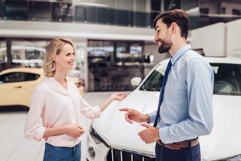 Πωλητής που μιλά με τη γυναίκα στο σαλόνι αντιπροσώπων στοκ φωτογραφία με δικαίωμα ελεύθερης χρήσης