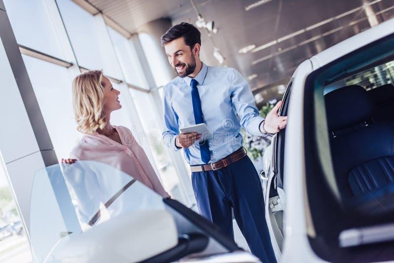 Πωλητής που παρουσιάζει νέο αυτοκίνητο στο θηλυκό πελάτη στοκ εικόνες