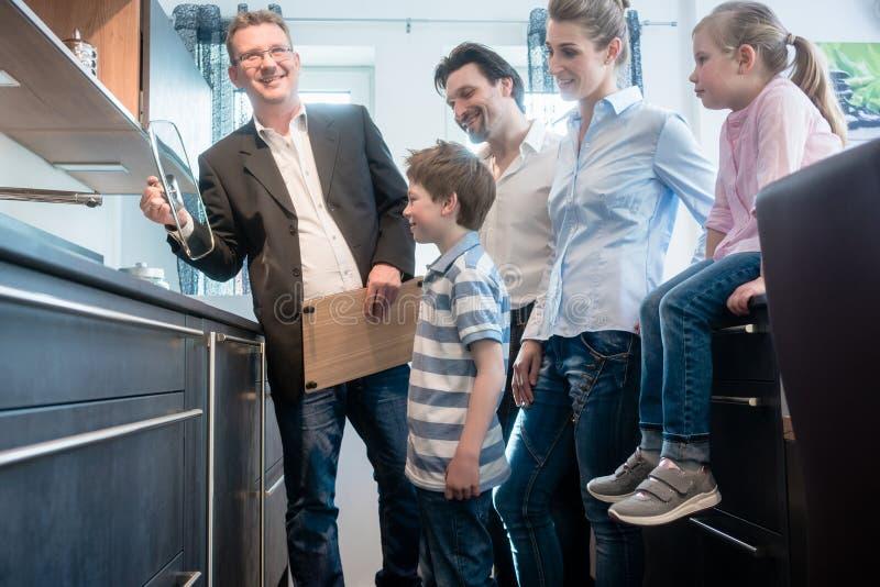 Πωλητής που παρουσιάζει στην οικογένεια τα χαρακτηριστικά γνωρίσματα μιας νέας κουζίνας στοκ φωτογραφίες