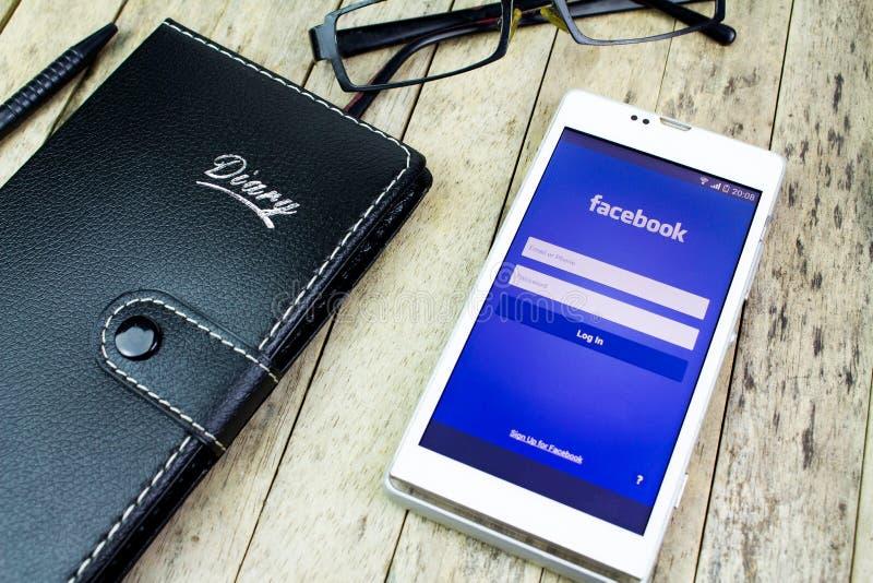 ΠΩΜΑ KAN, ΤΑΪΛΆΝΔΗ - 9 ΟΚΤΩΒΡΊΟΥ 2015: σημειωματάριο, γυαλιά, μάνδρα, έξυπνο τηλέφωνο με Facebook app στοκ εικόνα