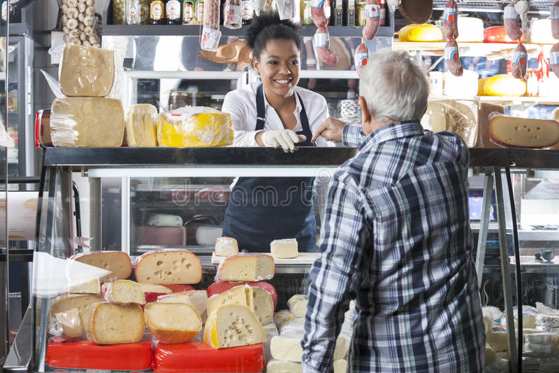 Πωλήτρια που παίρνει τη διαταγή από τον πελάτη στο κατάστημα τυριών στοκ εικόνα