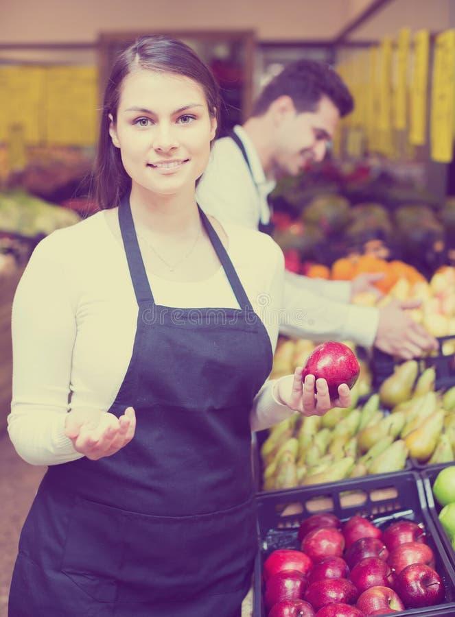 Πωλητές που προσφέρουν τα εποχιακά γλυκά μήλα στο παντοπωλείο στοκ εικόνες