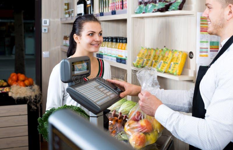 Πωλητής ατόμων που βοηθά τον πελάτη για να ζυγίσει τις αγορές στοκ εικόνες με δικαίωμα ελεύθερης χρήσης