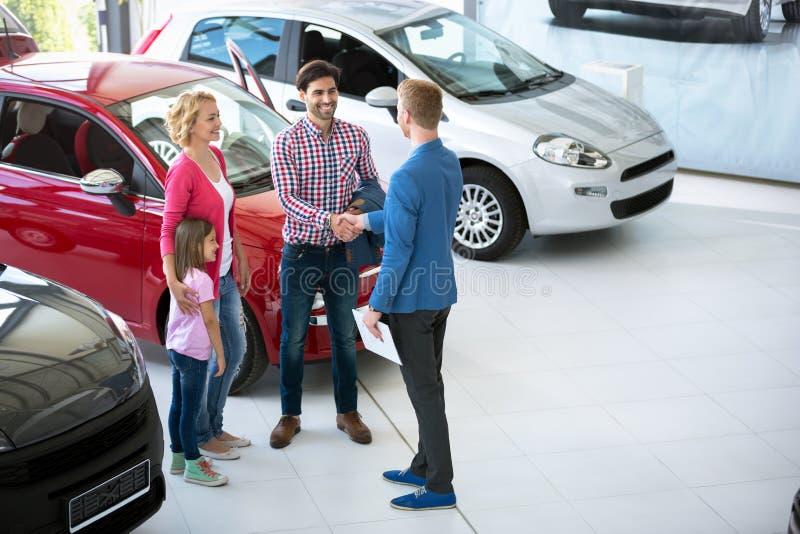 Πωλητής αυτοκινήτων που παρουσιάζει νέο όχημα στους πελάτες στοκ εικόνα
