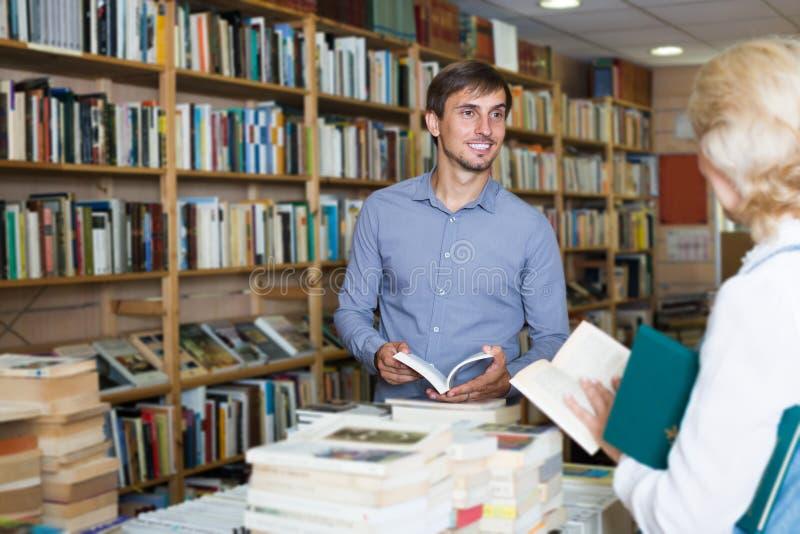 Πωλητής νεαρών άνδρων που βοηθά τον πελάτη στο κατάστημα βιβλίων στοκ εικόνα