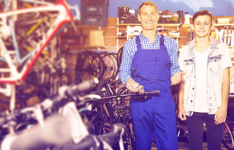 Πωλητής που βοηθά τον έφηβο για να αγοράσει το ποδήλατο στοκ φωτογραφίες