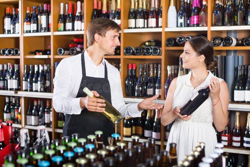 Πωλητής που βοηθά τον πελάτη γυναικών με το μπουκάλι του κρασιού στοκ εικόνα