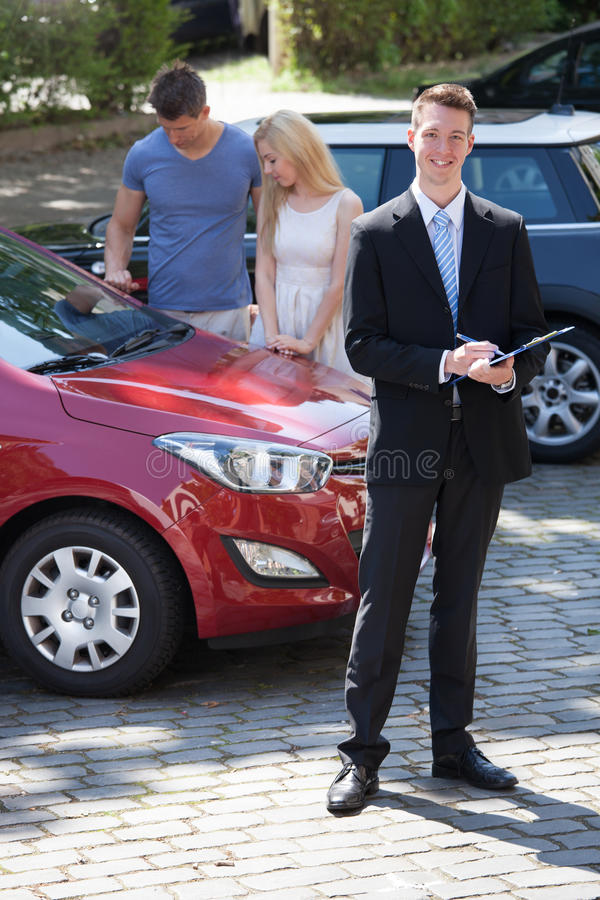 Πωλητής που γράφει στην περιοχή αποκομμάτων με το ζεύγος που εξετάζει το αυτοκίνητο στοκ φωτογραφία με δικαίωμα ελεύθερης χρήσης