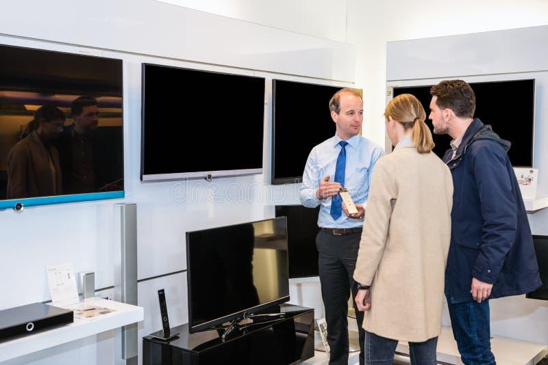 Πωλητής που παρουσιάζει επίπεδη τηλεόραση οθόνης για να συνδέσει στο κατάστημα στοκ φωτογραφίες