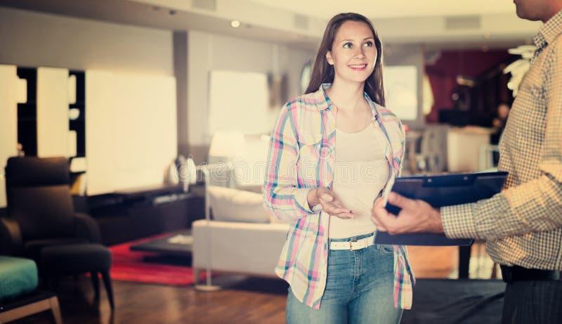 Πωλητής που προσφέρει τις παραλλαγές επίπλων στη γυναίκα στο σαλόνι στοκ εικόνα