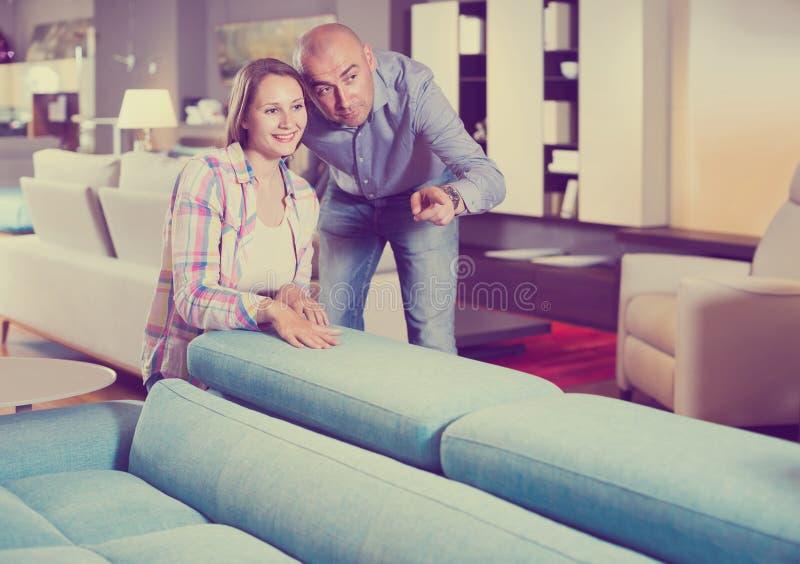 Πωλητής που προσφέρει τις παραλλαγές επίπλων στη θετική γυναίκα στο σαλόνι στοκ φωτογραφία