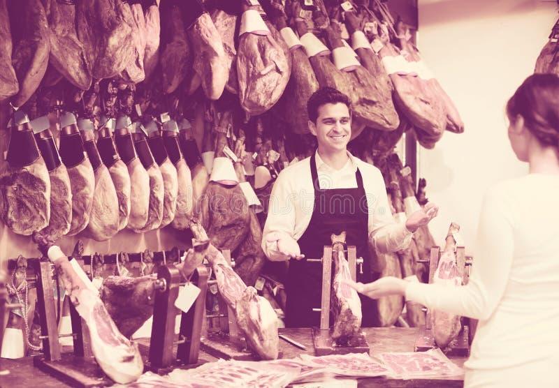 Πωλητής που προσφέρει jamon στον πελάτη στοκ φωτογραφίες