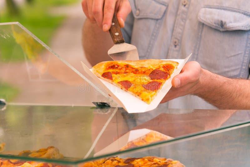 Πωλώντας πίτσα ατόμων από τη φέτα στοκ φωτογραφία