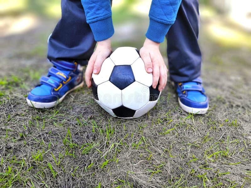 Πόδια αγοριών και χέρια εκμετάλλευσης σφαιρών στην πράσινη χλόη στοκ φωτογραφίες με δικαίωμα ελεύθερης χρήσης