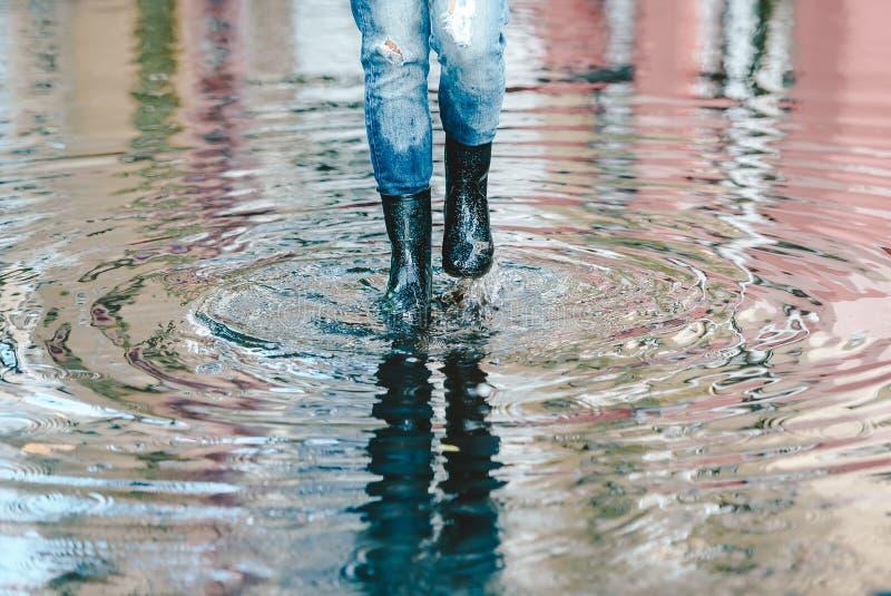 Πόδια γυναίκας με τις μαύρες λαστιχένιες μπότες και τζιν παντελόνι που στέκεται σε μια λακκούβα του νερού μετά από τη βροχή σε μι στοκ φωτογραφία με δικαίωμα ελεύθερης χρήσης