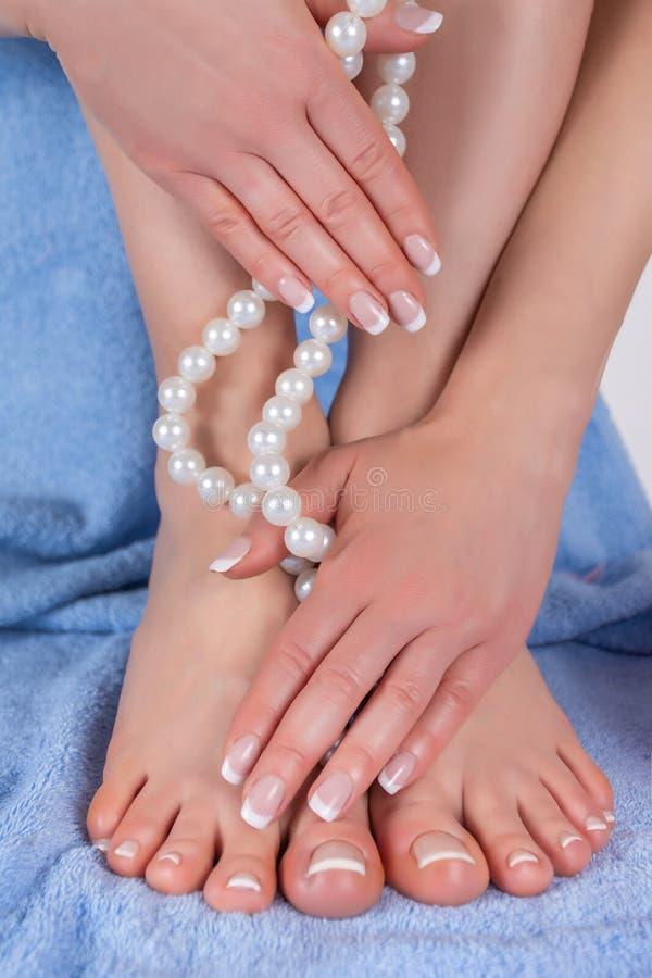Πόδια γυναικών μανικιούρ και pedicure με τα γυμνά πόδια και χέρια που κρατούν το περιδέραιο μαργαριταριών στην μπλε πετσέτα στο υ στοκ φωτογραφίες με δικαίωμα ελεύθερης χρήσης