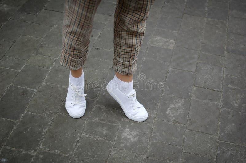 Πόδια γυναικών με τα άσπρα πάνινα παπούτσια και περιστασιακά εσώρουχα στο υπόβαθρο ασφάλτου κατά τη διάρκεια του χρόνου άνοιξης ή στοκ εικόνες