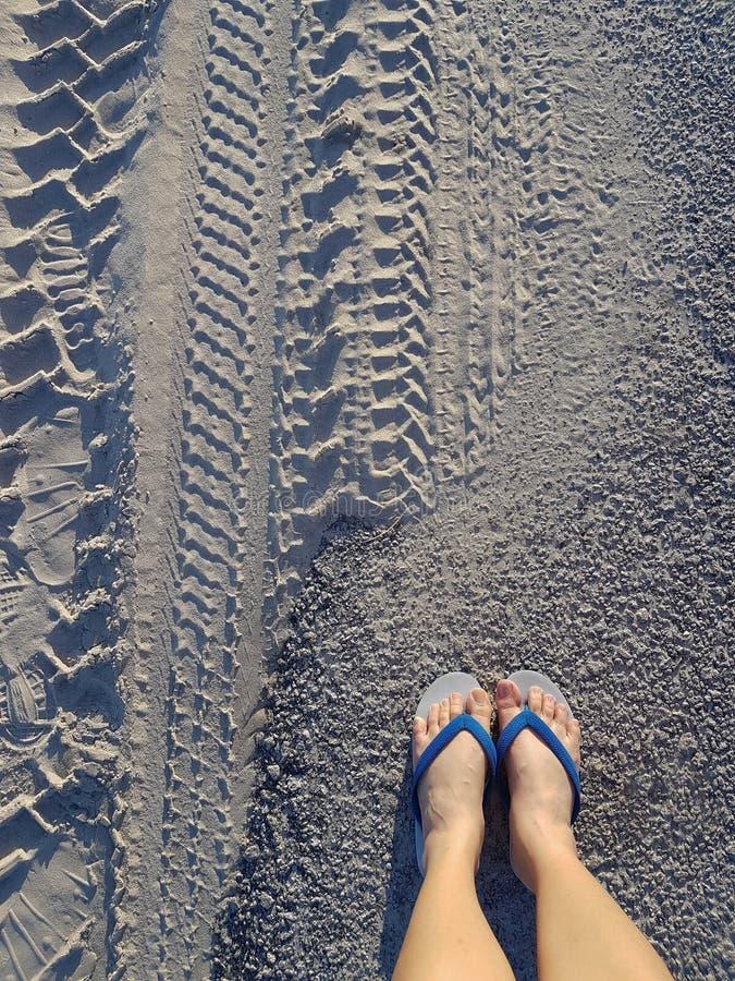 Πόδια γυναικών στα άσπρα και μπλε σανδάλια στην άμμο στοκ εικόνες