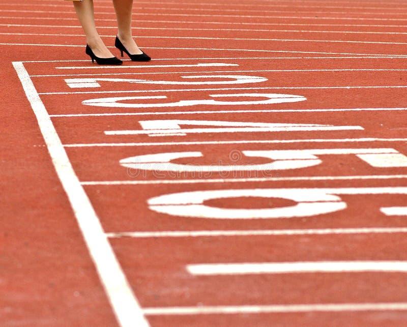 Πόδια γυναικών στα επίσημα παπούτσια που στέκονται στην κόκκινη τρέχοντας διαδρομή στοκ εικόνα