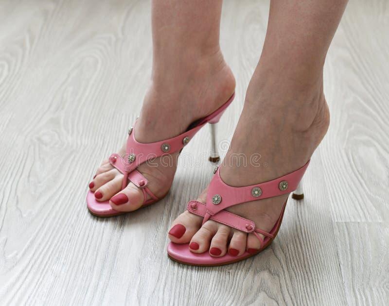 Πόδια γυναικών στα θερινά βαλμένα τακούνια ροζ σανδάλια στοκ εικόνες