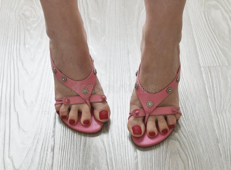 Πόδια γυναικών στα θερινά βαλμένα τακούνια ροζ σανδάλια στοκ φωτογραφία