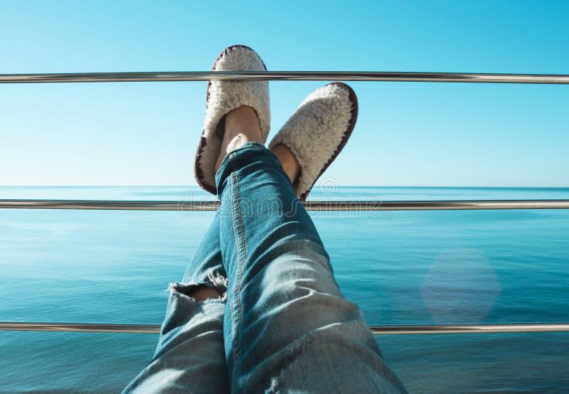 Πόδια γυναικών στα σχισμένα τζιν και τις άσπρες παντόφλες γουνών προβάτων που βρίσκονται στην εγκάρσια ράβδο του μπαλκονιού στοκ φωτογραφία