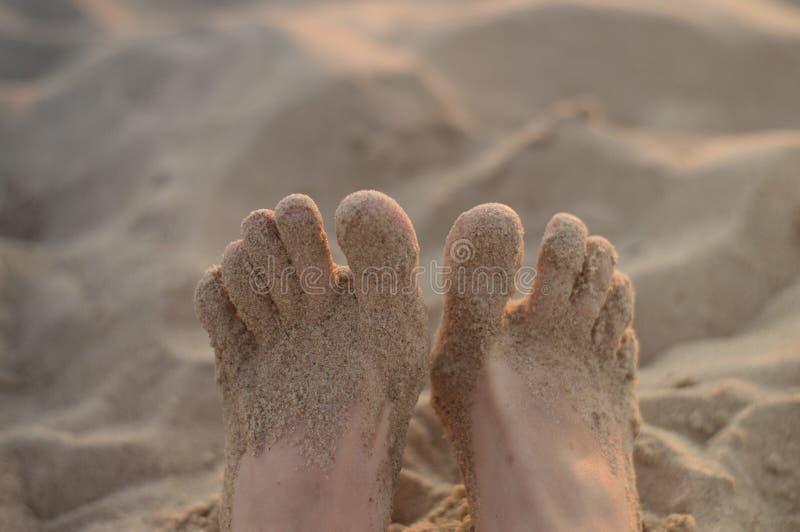 Πόδια γυναικών στην παραλία άμμου στοκ φωτογραφίες