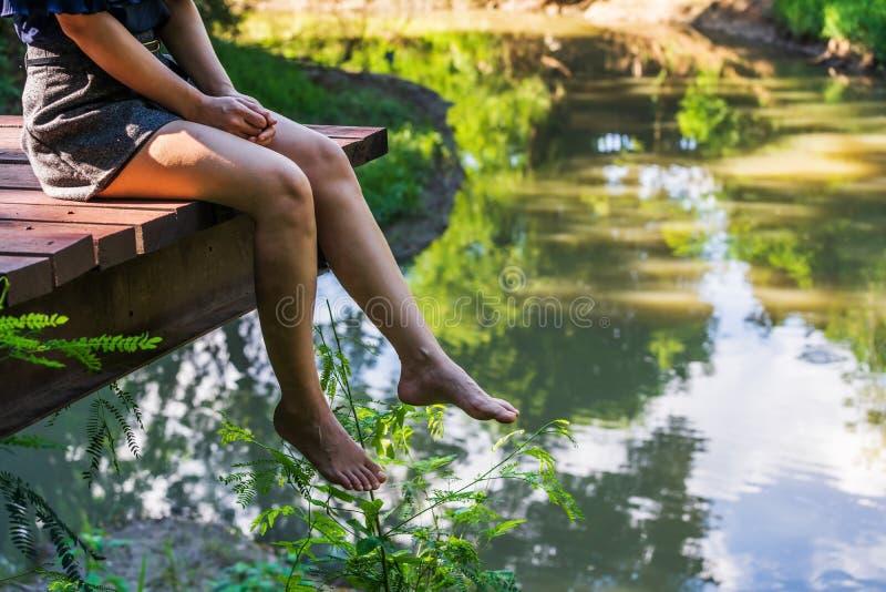 Πόδια γυναικών ` s που κρεμούν πέρα από την άκρη του ξύλινου λιμενοβραχίονα στοκ φωτογραφία με δικαίωμα ελεύθερης χρήσης