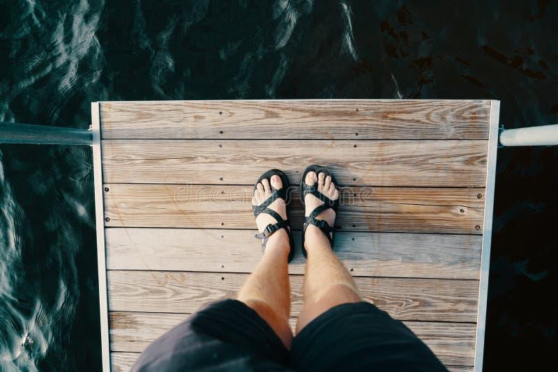 Πόδια ενός αρσενικού που στέκεται σε μια ξύλινη επιφάνεια πέρα από το σώμα του νερού στοκ εικόνες