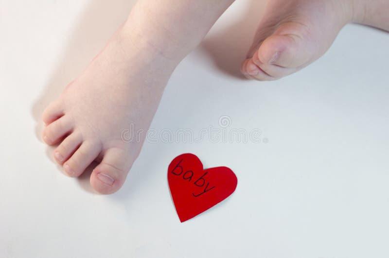Πόδια ενός παιδιού σε ένα άσπρο υπόβαθρο και μια κόκκινη καρδιά μικρά στοκ εικόνες