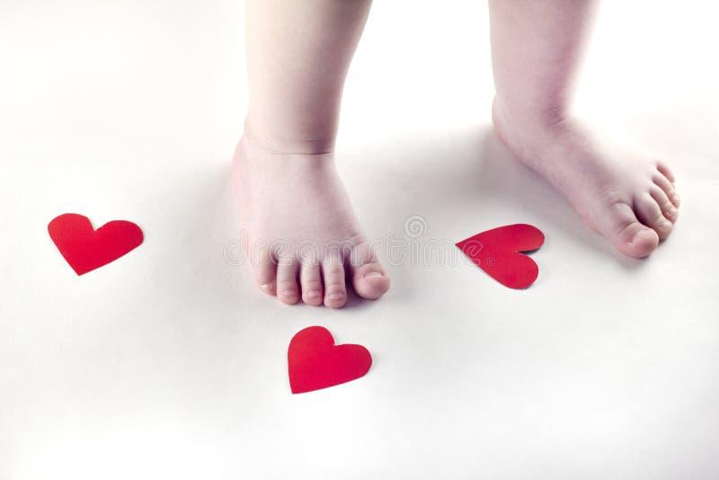 Πόδια και καρδιές μωρών σε μια άσπρη αγάπη υποβάθρου στοκ φωτογραφίες