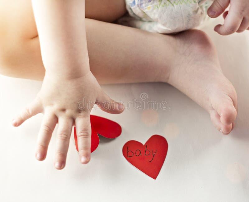 Πόδια και καρδιές μωρών στο άσπρο υπόβαθρο, ήλιος, κινηματογράφηση σε πρώτο πλάνο, καρδιές στοκ φωτογραφία με δικαίωμα ελεύθερης χρήσης