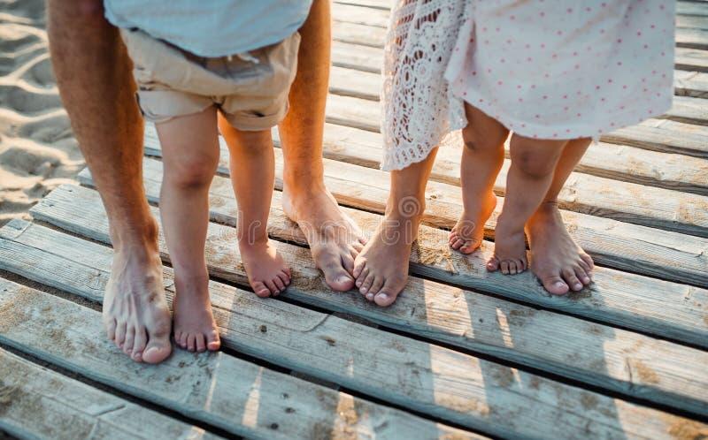 Πόδια και πόδια της οικογένειας που στέκονται στην παραλία στις καλοκαιρινές διακοπές, midsection στοκ φωτογραφίες