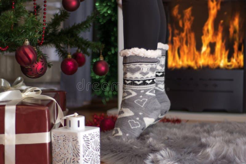 Πόδια κοριτσιών στην υποδοχή Χριστουγέννων που στέκεται στα δάχτυλα κοντά στην εστία στοκ φωτογραφία με δικαίωμα ελεύθερης χρήσης