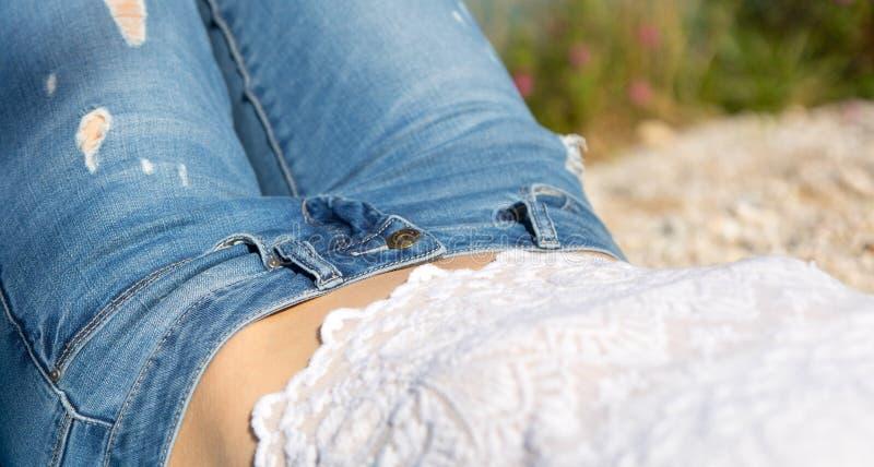 Πόδια με το τζιν παντελόνι ενός κοριτσιού που περνά το ελεύθερο χρόνο της στην παραλία χαλικιών στοκ φωτογραφία με δικαίωμα ελεύθερης χρήσης