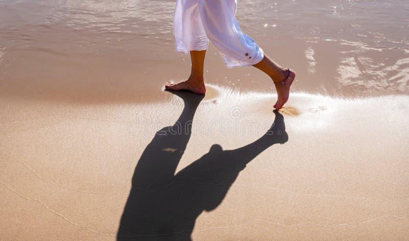 Πόδια μιας γυναίκας που περπατά σε μια αμμώδη παραλία στοκ εικόνες με δικαίωμα ελεύθερης χρήσης