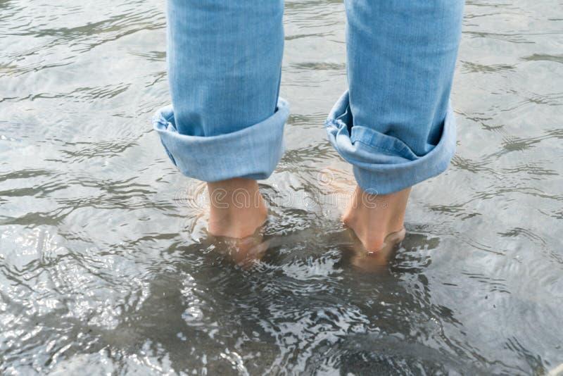 Πόδια μιας γυναίκας στο κρύο νερό ποταμού κατά τη διάρκεια ενός Kneipp footb στοκ εικόνα