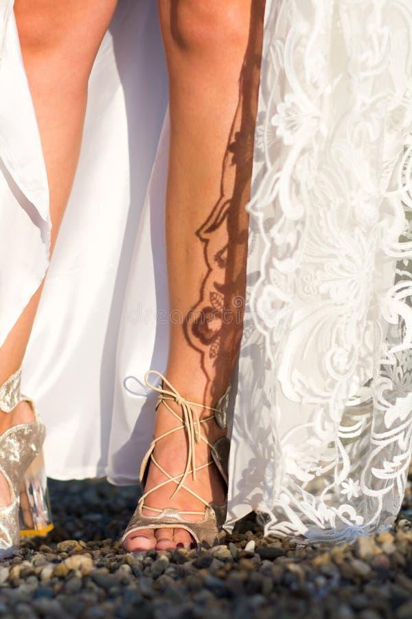 Πόδια μιας νύφης στο γαμήλιο φόρεμα στοκ φωτογραφίες
