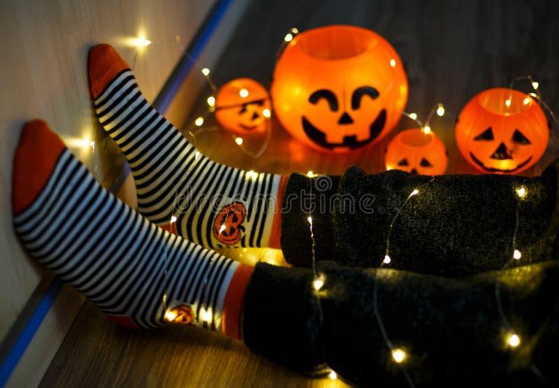Πόδια παιδιών στις μοντέρνες θερμές φωτεινές ζωηρόχρωμες ριγωτές αστείες κάλτσες στα φω'τα γιρλαντών στο πάτωμα με τις κολοκύθες  στοκ εικόνες