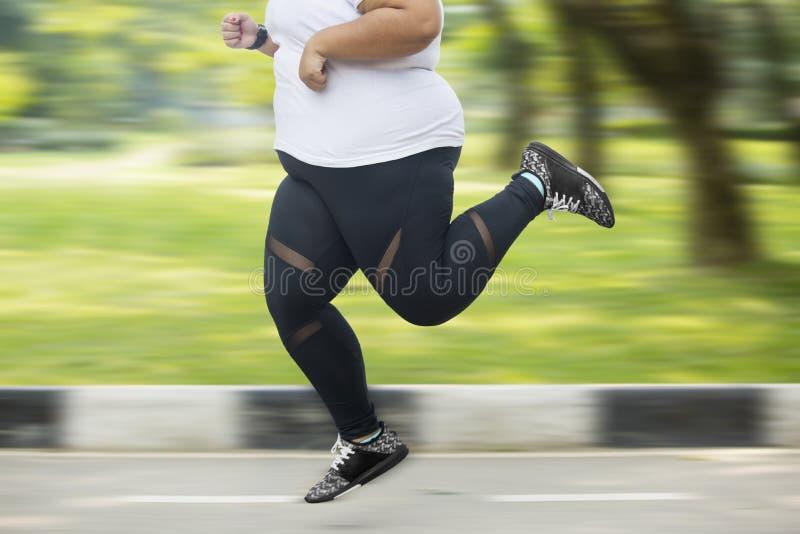 Πόδια παχύσαρκο να τρέξει γρήγορα γυναικών στο δρόμο στοκ φωτογραφίες