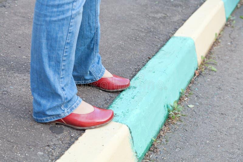 Πόδια στα κόκκινα παπούτσια στο αστικό πεζοδρόμιο στην ημέρα φθινοπώρου στοκ εικόνα