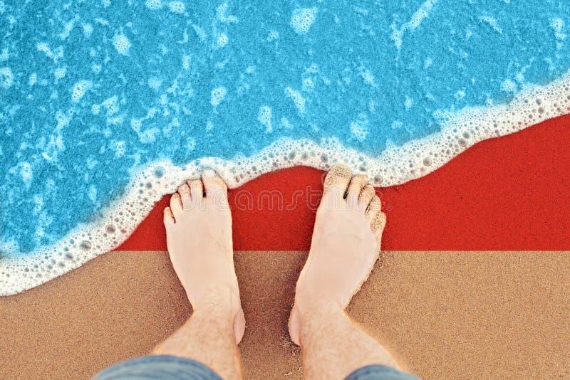 Πόδια στην αμμώδη παραλία με τη σημαία Ινδονησία Τοπ άποψη σχετικά με την κυματωγή στοκ φωτογραφία