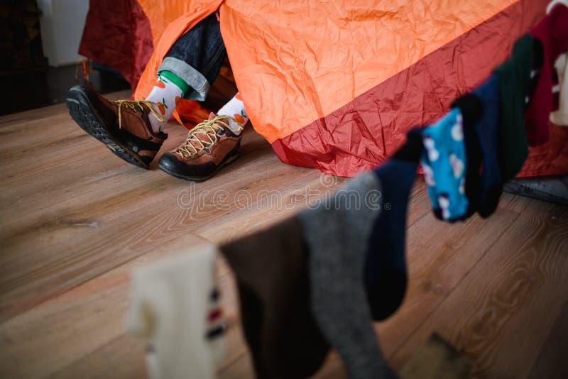 Πόδια στις ευτυχείς κάλτσες Το άτομο χαλαρώνει κοντά στη σκηνή και θερμαίνει τα πόδια του στις ευτυχείς κάλτσες στοκ εικόνες με δικαίωμα ελεύθερης χρήσης