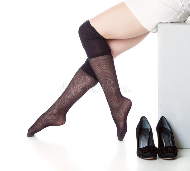 Πόδια στις μαύρες γυναικείες κάλτσες στοκ εικόνα