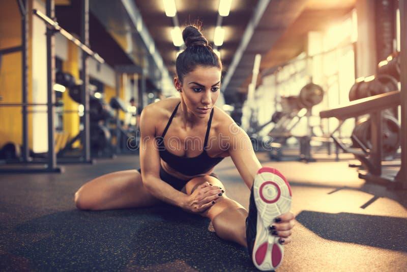 Πόδια τεντώματος γυναικών στο κέντρο ικανότητας στοκ φωτογραφία με δικαίωμα ελεύθερης χρήσης