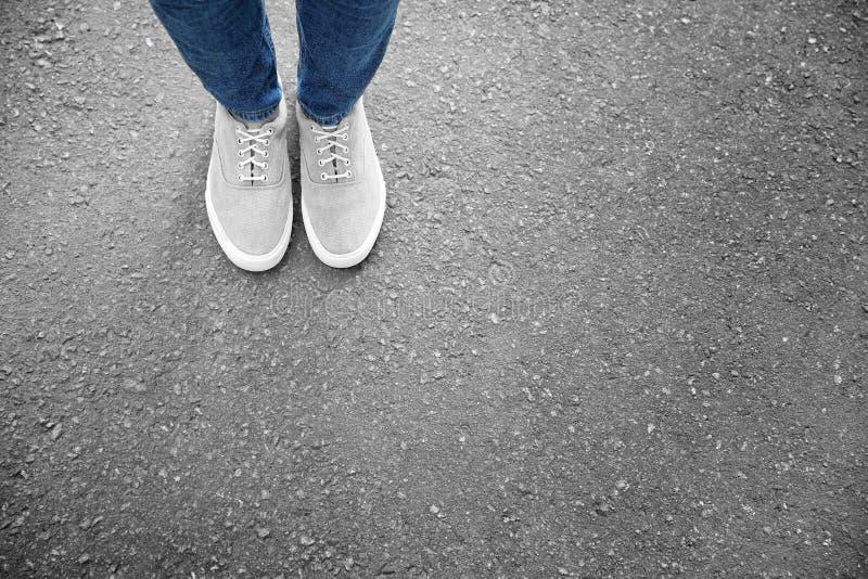 Πόδια της γυναίκας στα περιστασιακά παπούτσια στην άσφαλτο στοκ φωτογραφία